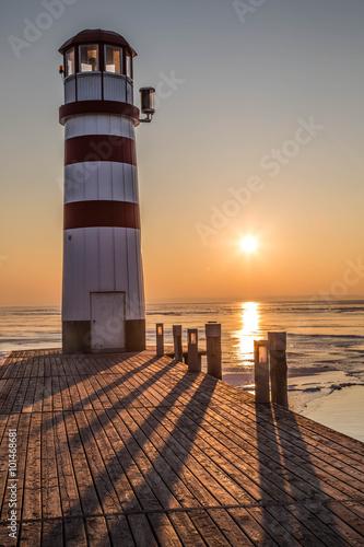 Foto op Aluminium Vuurtoren Holzsteg mit Leuchtturm im Winter vor gefrorenem See im Sonnenuntergang