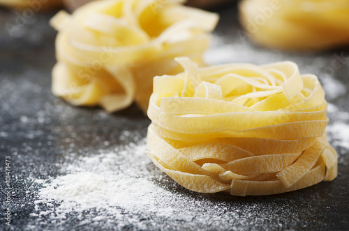 Fotografiet  Uncooked pasta with flour on the table