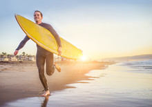 Surfer Running On The Beach