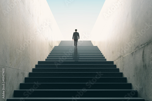 Valokuva  Ambitions concept with businessman climbing stairs