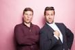 Zwei coole Typen posieren vor rosa Hintergrund