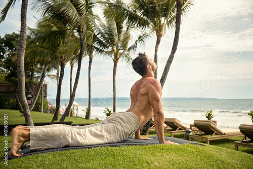 Fotografie, Tablou  fit young man doing the cobra pose in nature