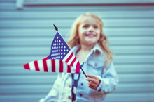 Flying American Flag In Little Girl's Hand. Selective Focus, Blurred Background. Independence Day, Flag Day Concept. Vintage And Retro Toning