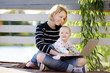 Young mother with her baby working or studying on laptop