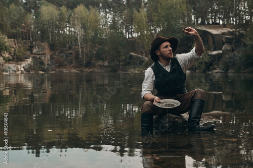 Fotografia, Obraz  unshaved golddigger washes gold in the lake with rocky bank