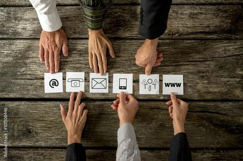 Láminas  Seis personas colocando tarjetas en blanco con varios iconos de contacto en Arka