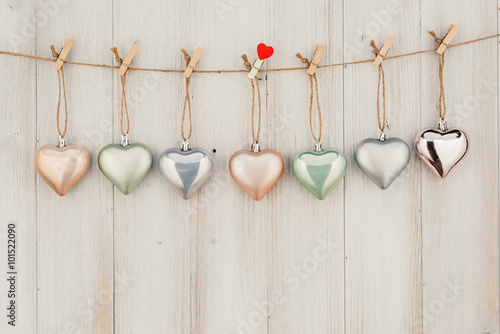Heart hanging on the clothesline. On old wood background