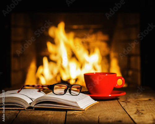 Photo Red cup of coffee or tea, glasses and old book on wooden table n