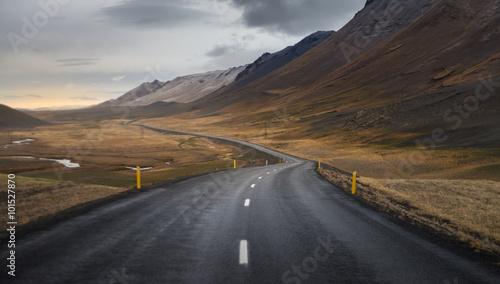 ciemna-asfaltowej-drogi-perspektywa-z-koloru-zoltego-pola-wzgorza-i-pasma-gorskiego-tlem-w-jesien-sezonie-iceland