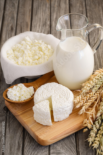 Staande foto Zuivelproducten Fresh dairy products. Milk and cottage cheese with wheat on the rustic wooden background.