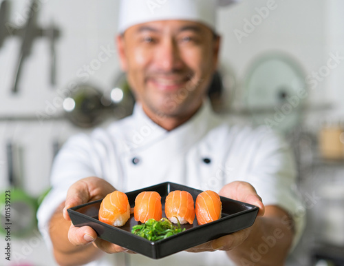 Poster Sushi bar Smiling asian chef with sushi. Focus on sushi