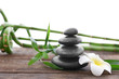 Spa stones with bamboo and tropical flower on white background