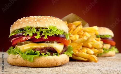 Fototapeta Cheeseburger and french fries on red spotlight on wooden table obraz