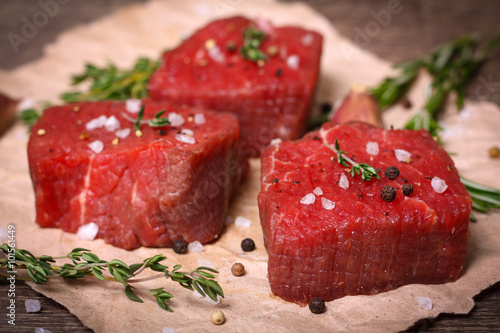 Staande foto Vlees Raw beef steak with rosemary, thyme and garlic on wooden background