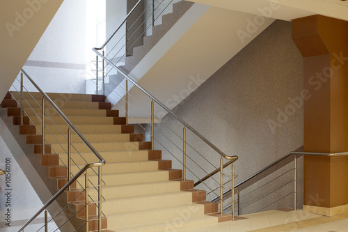 Photo Stands Stairs Brown staircase with metal railing, gray wall