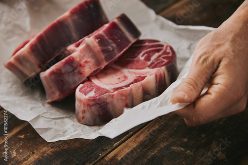 Closeup hand holds white paper three raw steaks Tablou Canvas