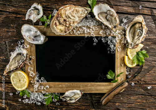 Poster Coquillage Oysters served on wood with blackboard