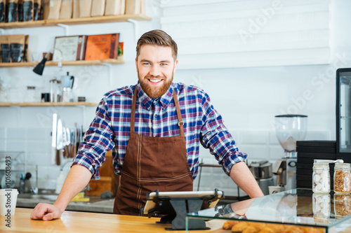 Fotografie, Obraz  Happy handsome barista in checkered shirt and brown apron