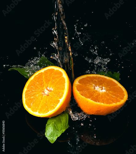 Pomarańcze polane wodą na czarnym tle