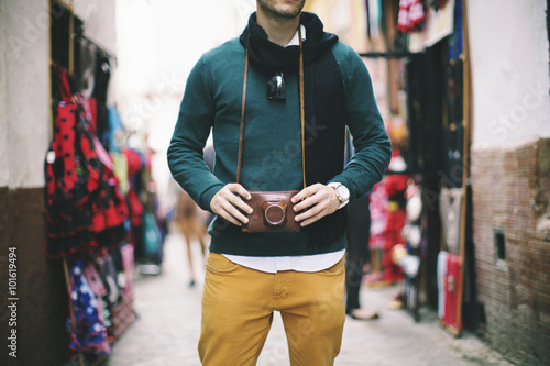 Young man holding a vintage retro camera, Seville, Spain