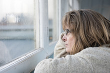 Portrait Image Of A Fed Up Mature Woman Looking Out Of The Window On A Rainy Miserable Day