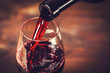 canvas print picture - Pouring red wine into the glass against wooden background