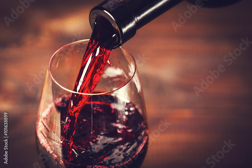 Fotografie, Obraz  Pouring red wine into the glass against wooden background