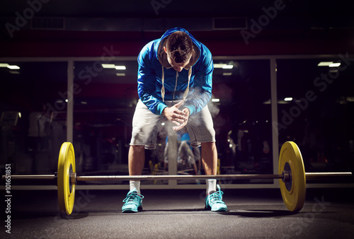 Fotografia  Cross fit weightlifter preparing for training