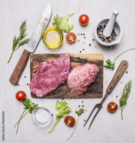 Staande foto Vlees raw Pork steak with vegetables and herbs, meat knife and fork, on a cutting board on wooden rustic background top view close up