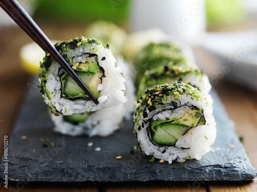 Poster de jardin Sushi bar healthy kale and avocado sushi roll with chopsticks