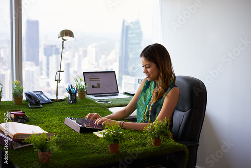 Fotografía  Environmentalist Woman Types Email With Tablet On Office Desk