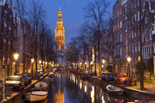 Poster Amsterdam Church and a canal in Amsterdam at night
