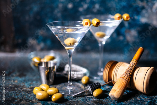 Fotografía  Martini cocktail drink with olives garnish and tools on rusty background