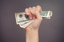 Woman Hand Squeezes Dollar Bills