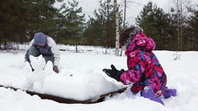 Grandmother Making Snowman With Young Granddaughter At Winter
