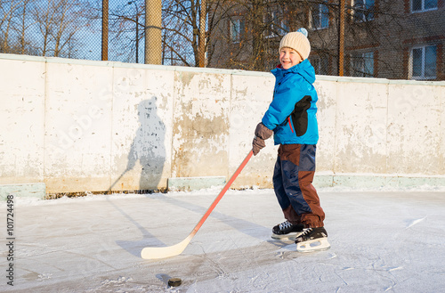 Winter Time Young Smiling Boy Playing Ice Hockey On An Outdoor Ice