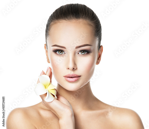 Beautiful face of young woman with flower