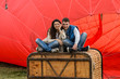 canvas print picture - Young couple sitting near the balloon
