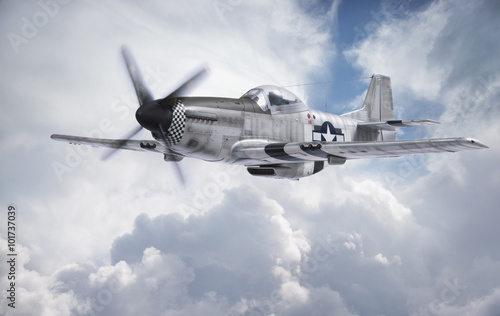 Photo World War II era fighter flies among clouds and blue sky
