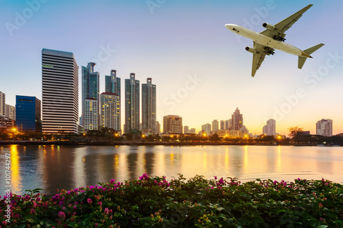 Photo  Modern building with flower and airplane under the sky at twilig
