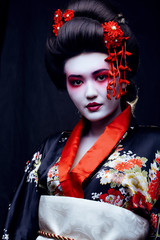 Fototapetayoung pretty geisha in kimono with sakura and decoration