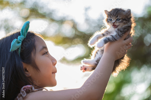 Little Asian girl holding Lovely persian kitten with sunshine in the park Canvas Print