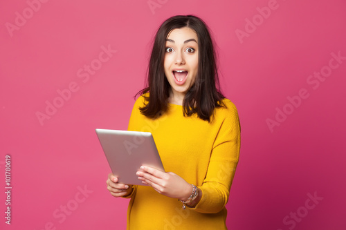 Fotografía  Surprised young woman holding tablet computer