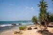 Ein Traumstrand am Indischen Ozean mit strahlend blauem Himmel und einem türkis-blau funkelnden Ozean mit Kokospalmen am feinen Sandstrand