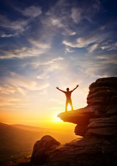 A person reaching up from a high point, set against a sunset. Expressing freedom