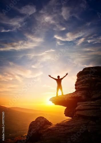 Fotografía  Una persona que alcanza hasta desde un punto alto, frente a una puesta de sol