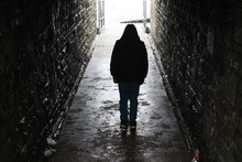 Hooded Boy Silhouetted In An Underground Tunnel
