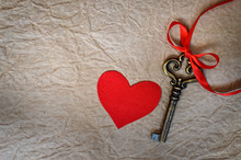 Red Fabric Heart And Key On Grunge Paper Background