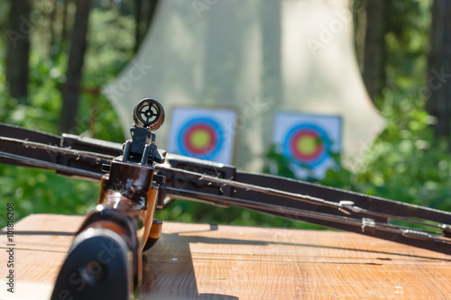Canvas Print Crossbow lying on a table with targets at backgroung