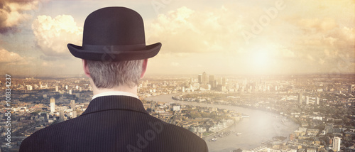 Obrazy na płótnie Canvas Businessman looking at sunset above city skyline